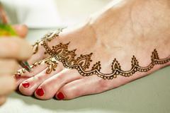 Mehendi. Master applying henna on model's leg Stock Photos