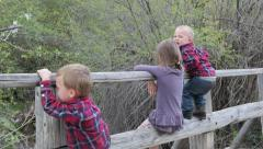Kids sitting on bridge Stock Footage