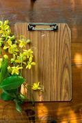 clipboard on grungy wooden surface, with plenty of copy space. - stock photo