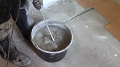 Man mix cement in bucket. Preparation for glue tiles in kitchen Stock Footage