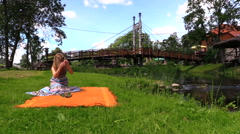 Woman prepare picnic place on orange plaid rug near river water Stock Footage