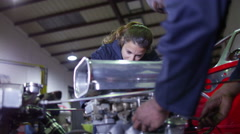 4K Team of male and female mechanics working on a car engine in garage workshop Stock Footage
