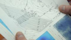 Forecaster stapling weather charts - stock footage
