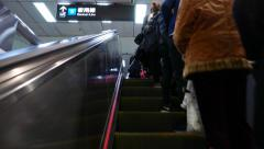 Walking up escalator at metro station, passengers standing on right Stock Footage