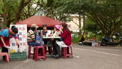 Open air eatery in park, woman sitting at a table on the street Stock Footage