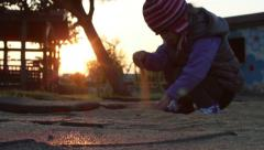 Little girl playing in sandpit at the sunset time 1 - Model Release Stock Footage