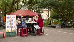 Noshery with cheap food, table and four asian women sitting around Stock Footage