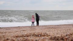 Mother and Daughter Watch Waves Crashing on Shingle Beach Stock Footage