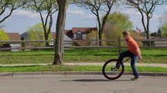 Young man getting on unicycle and riding in slow motion 4K Stock Footage