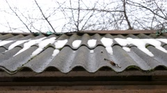 Thaw. Water from melting snow and ice drips from asbestos roof Stock Footage