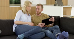Attractive young couple in living room, play fight over tablet Stock Footage