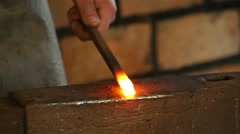 blacksmith has an effort on glowing hot metal and sparks fly in all directions - stock footage