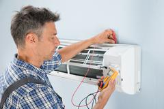 Portrait Of A Mid-adult Male Technician Testing Air Conditioner With Digital  - stock photo