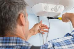 Close-up Of Mid-adult Male Plumber Installing Water Heater Stock Photos