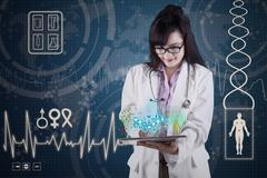 Doctor with medical apps on digital tablet Stock Photos