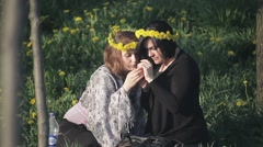 Girls sitting on the lawn and making wreaths Stock Footage