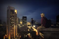 Traveller Sitting On The Top Of Building - stock photo