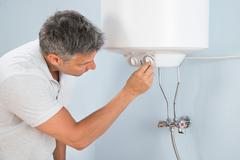 Portrait Of A Mid-adult Man Adjusting Temperature Of Electric Boiler Stock Photos