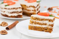 Delicious slice of carrot sponge cake with icing cream and little orange carrots - stock photo
