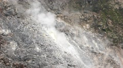Opaque white smoke rises from the dry fumarole, stony inclined slope - stock footage