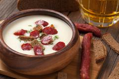 Bowl of white cream beer soup with sausage and croutons on woode - stock photo
