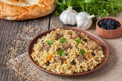 Arabic traditional rustic rice food pilaf cooked with fried meat, onion, carrot - stock photo