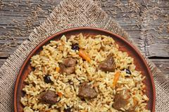 Bowl of arabic national rice food pilaf with fried meat, healthy onion, carrot - stock photo