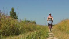 Woman Riding Her Bike along the field - panoramic movements Stock Footage