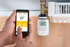 Close-up Of Person's Hand Adjusting Temperature Of Thermostat Using Cellphone - stock photo