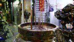 Incense sticks in urn with dragons in front of religion shop Stock Footage