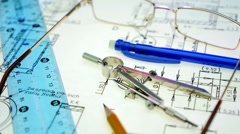 Pen, pencil, compass, ruler and glasses lie on the drawing Stock Footage