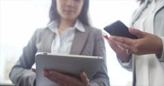 4K Close up on the hands of 2 businesswomen using mobile technology outdoors Stock Footage