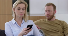 Attractive woman chats on cell phone, annoying her boyfriend in contemporary - stock footage