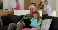 Grandfather plays game on electronic tablet with granddaughters Stock Footage