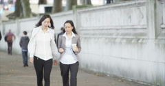 4K 2 Attractive Asian businesswomen chat together as they walk through the city Stock Footage