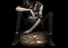 Young woman poses as drug addict. Stock Photos