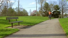 Rider smiles as they pedal unicycle past camera 4K - stock footage