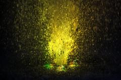Colorful fountain splashes yellow color - stock photo