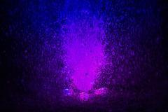 Colorful fountain splashes violet and blue color - stock photo