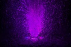 Colorful fountain splashes violet color - stock photo