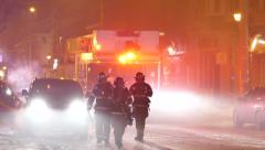 Fire fighters walking towards camera with smoke and firetruck with lights Stock Footage