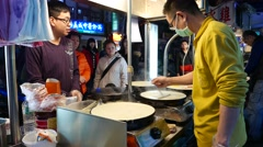 Chinese pancake cooking on night street, from behind the kitchener Stock Footage