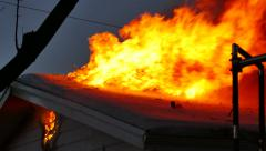 Heavy flames coming out of house roof covered in snow at night - Commercial Stock Footage
