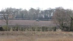Wide Shot of Green Tractor and Equipment on Ploughed Field on Rural Farm Stock Footage