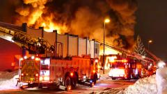 Huge inferno with firemen unrolling fire hoses with heavy flames - Commercial - stock footage