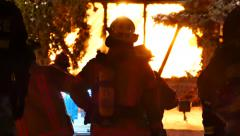 Fire fighters looking towards building on fire with flames - Commercial Stock Footage