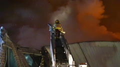 Fireman climbing ladder above building fire with structural damage - Commercial - stock footage
