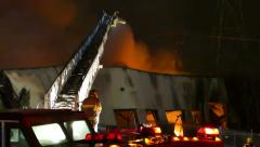 Fireman putting water on commercial building fire with aerial ladder Stock Footage