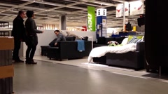 Customer shopping sofa bed inside Ikea store Stock Footage