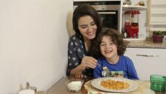 Eat meals to child mothers. mother with son eating lunch at home. Stock Footage